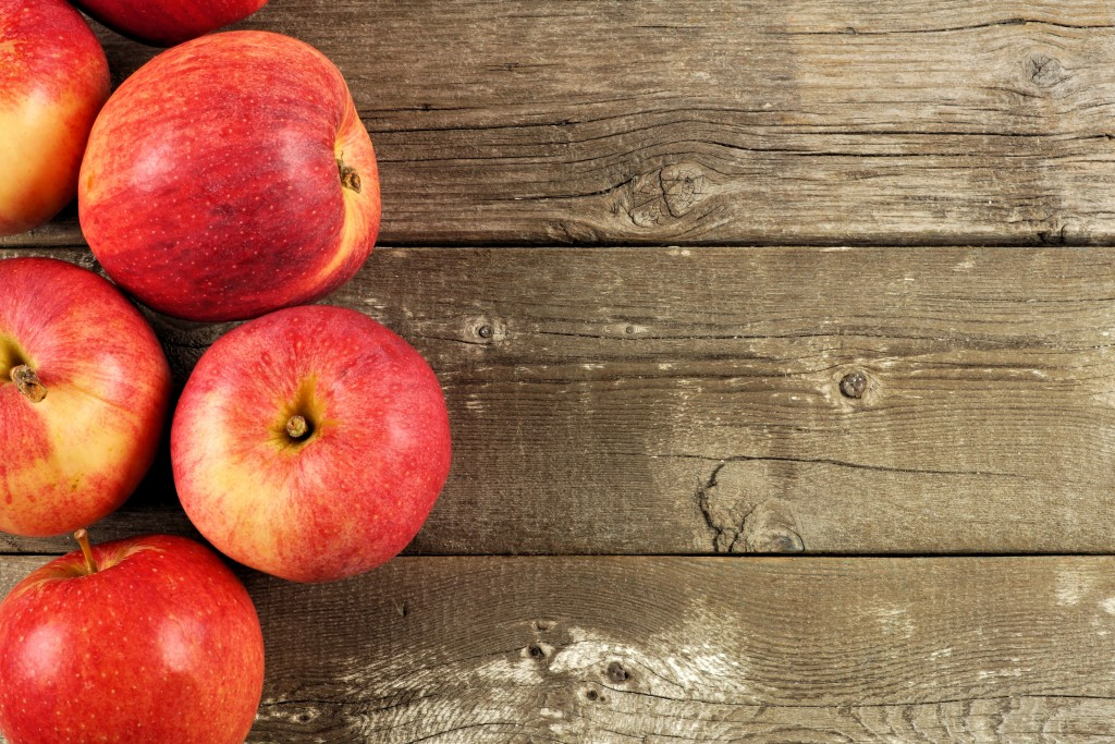 Freshly harvested apples, side border on rustic aged wood background